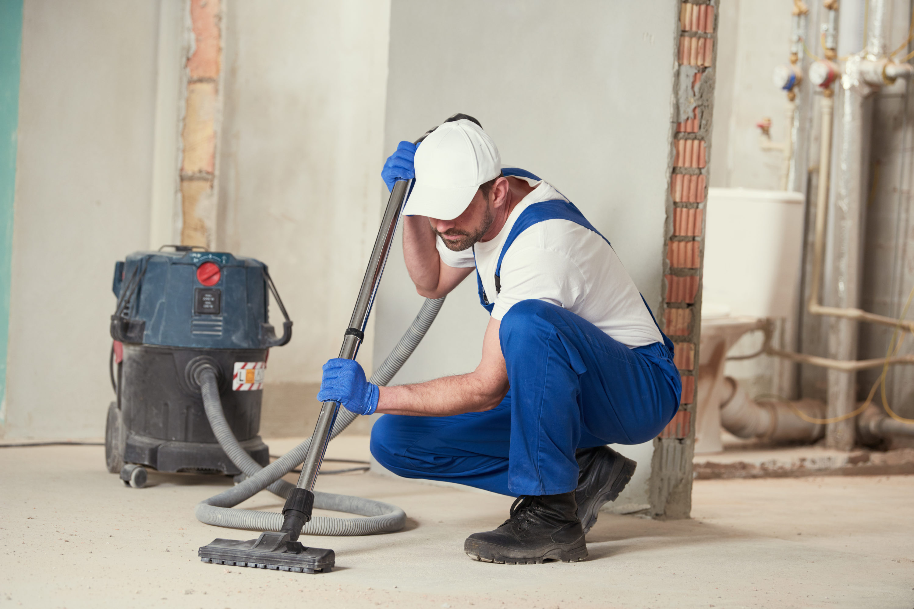 We provide a quality, reliability and friendly service. Maid to Order construction cleaning services - man vacuuming construction site.
